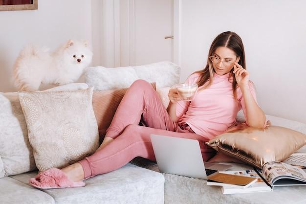 Una ragazza in pigiama a casa sta lavorando su un laptop con il suo cane spitzer, il cane e il suo proprietario stanno riposando sul divano e guardano il laptop.