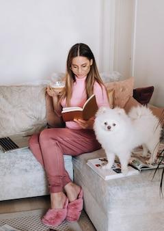 Una ragazza in pigiama a casa legge un libro con il suo cane spitzer, il cane e il suo proprietario stanno riposando sul divano e leggono un libro.