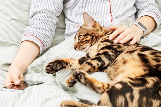 Ragazza in pigiama sdraiata a letto con il suo gatto bengala preferito.