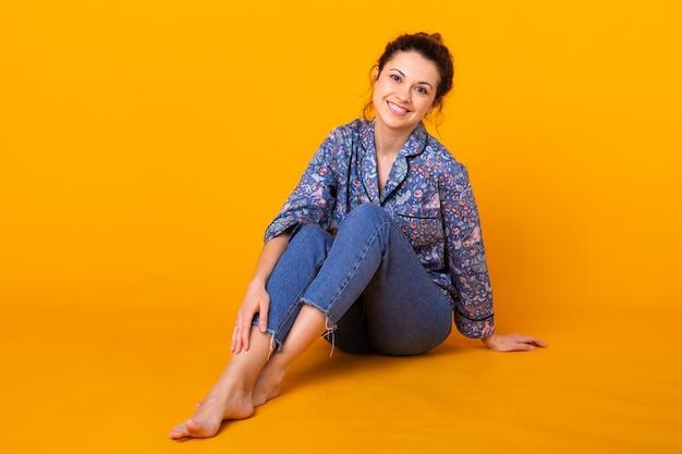 Ragazza in pigiama in posa mentre riposa a casa su sfondo giallo