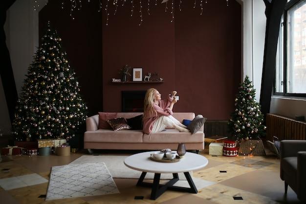 Ragazza in pigiama con una tazza di caffè si siede sul letto vicino all'albero e caminetto in un interno buio