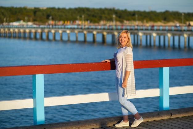 Una ragazza in pantaloni e giacca si trova su un molo vicino al mar baltico