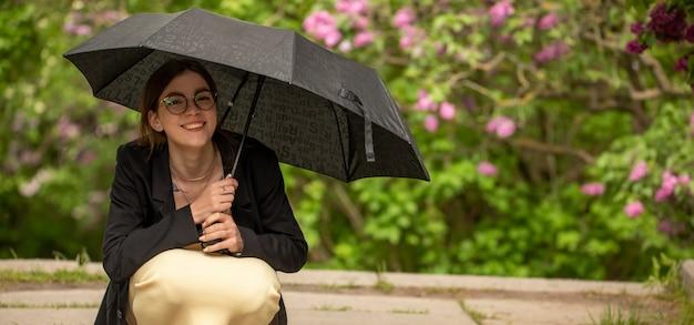 Ragazza nel parco durante la pioggia sotto l'ombrellone