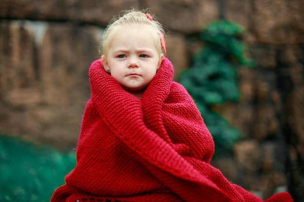 Ragazza nel parco avvolta in uno scialle di lana