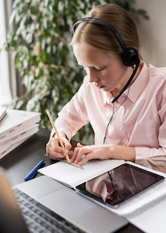 Ragazza che partecipa a una lezione online mentre prende appunti