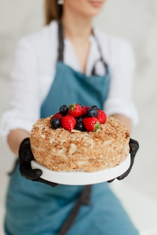Ragazza pasticcere tenendo la torta di miele con frutti di bosco cibo dolce