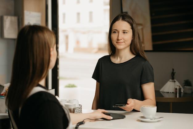 Una ragazza che paga per il suo caffè con uno smartphone con tecnologia nfc senza contatto in un caffè