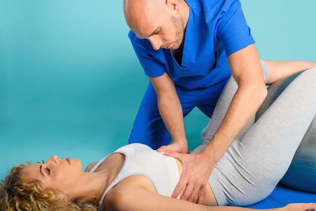 La ragazza esegue gli esercizi con un fisioterapista. sfondo ciano