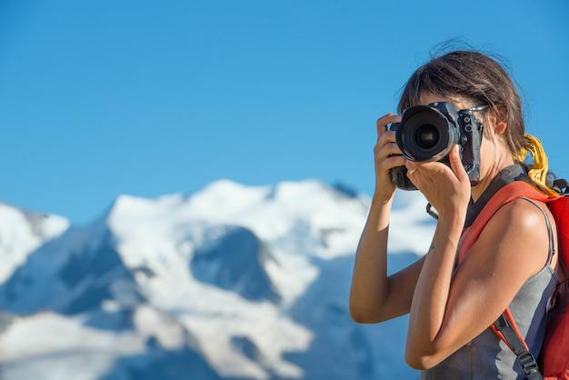 Ragazza che fotografa in alta montagna Foto Premium