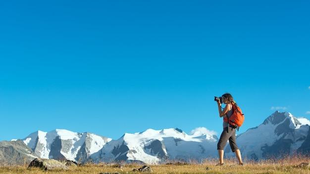La ragazza fotografa le alte montagne delle alpi