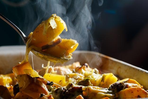 La ragazza prende un cucchiaio di patate al forno con funghi e formaggio