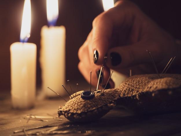 Una ragazza perfora una bambola voodoo con gli aghi, primo piano. rituali esoterici e occulti su un tavolo di legno in una stanza buia con molte candele.