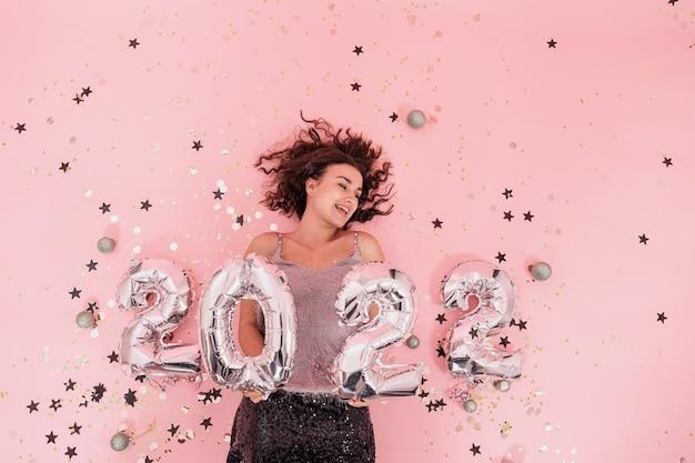 Una ragazza su uno sfondo rosa con palloncini d'argento dalla vista dall'alto dei numeri