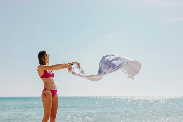 Ragazza in bikini rosa con un asciugamano in spiaggia