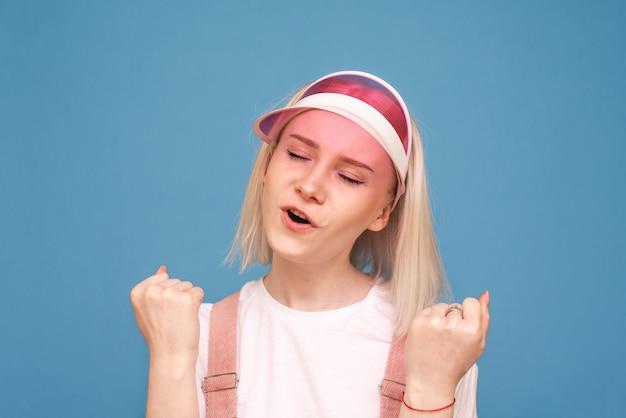 Ragazza con un berretto rosa e abiti luminosi gioisce sulla parete blu