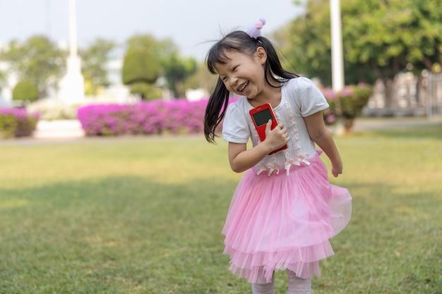 Un abito rosa ragazza felicemente in esecuzione in giardino