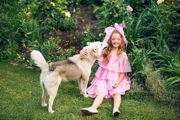 Una ragazza in abito rosa si siede sull'erba e gioca con un grosso cane