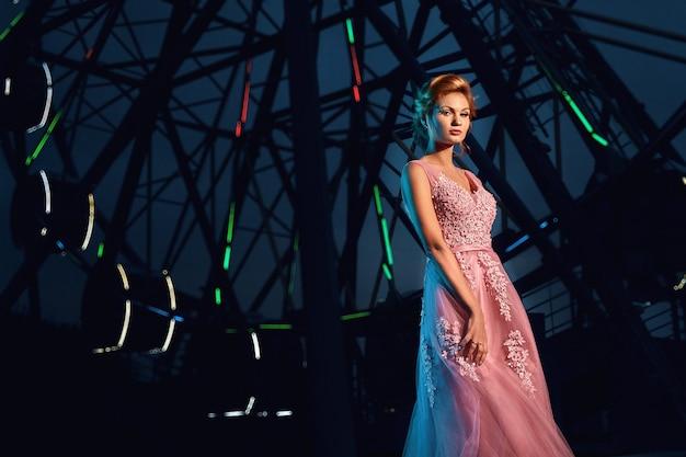 La ragazza in un abito da sera rosa con trucco e capelli è evidenziata con lampi di filtri in gel la sera sullo sfondo della ruota panoramica all'aperto.