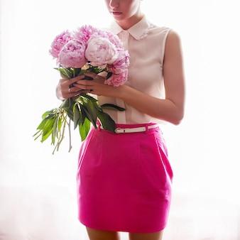 Ragazza in gonna rosa e giacca bianca nelle mani che tengono un mazzo di peonie su un muro bianco