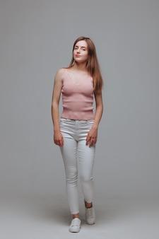 Ragazza in maglietta rosa e pantaloni bianchi su sfondo grigio