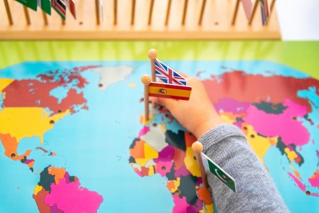 Ragazza che posiziona le bandiere di europa e spagna su una mappa