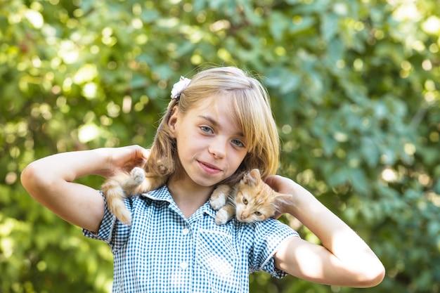 La ragazza gioca con il gattino all'aperto nel parco Foto Premium