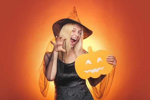 La ragazza gioca con le zucche e mangia. buon fine settimana di halloween. cappello da strega. felice halloween con zucche su uno sfondo di halloween. sfondo dell'orrore. facce da orrore. festa di halloween.