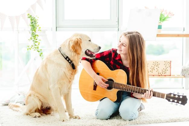Ragazza che gioca la chitarra con il cane adorabile