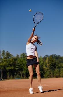 Una ragazza che gioca a tennis sul campo in una bella giornata di sole