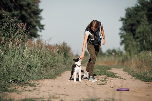 Ragazza che gioca con il cucciolo di cane border collie bianco e nero sulla strada forestale