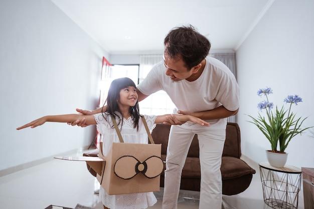 Ragazza che gioca con l'aeroplano giocattolo di cartone a casa con il padre