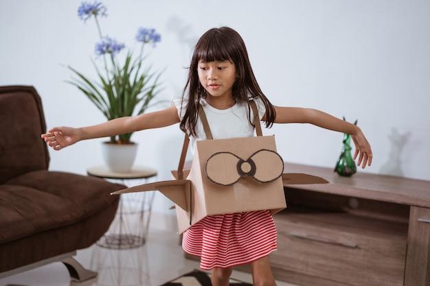 Ragazza che gioca con l'aeroplano giocattolo di cartone a casa
