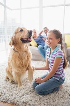 Ragazza che gioca con il cane mentre i genitori si rilassano a casa