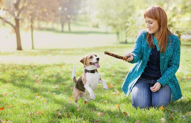 Ragazza che gioca con il suo cane nel parco di autunno