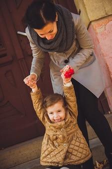 Ragazza che gioca con sua madre vicino alla vecchia porta donna sorridente che salta con sua figlia dalle scale
