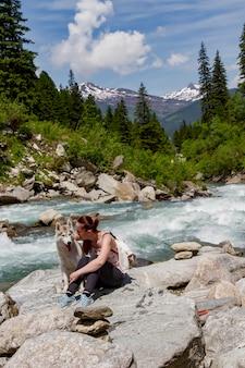 Ragazza che gioca con un cane husky sulla riva di un fiume di montagna