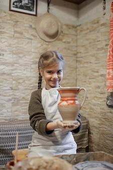 Ragazza che gioca con l'argilla per modellare sul tornio in ceramica in officina, artigianato artistico, hobby artigianale e tempo libero