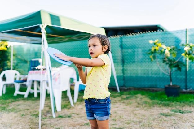 Una ragazza gioca a beach tennis in un giardino con piscina e giocattoli in estate