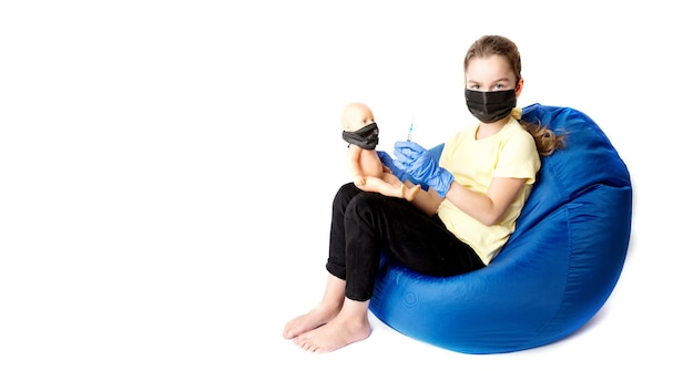 La ragazza interpreta un dottore con una bambola. la realtà del coronavirus nella vita dei bambini. iniezione contro covid19. foto di alta qualità