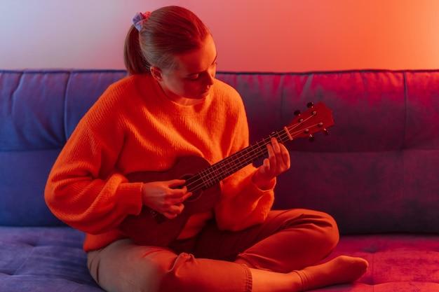 Una ragazza suona un ukulele sotto una luce multicolore