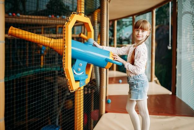 La ragazza gioca con la pistola ad aria compressa nel centro giochi per bambini