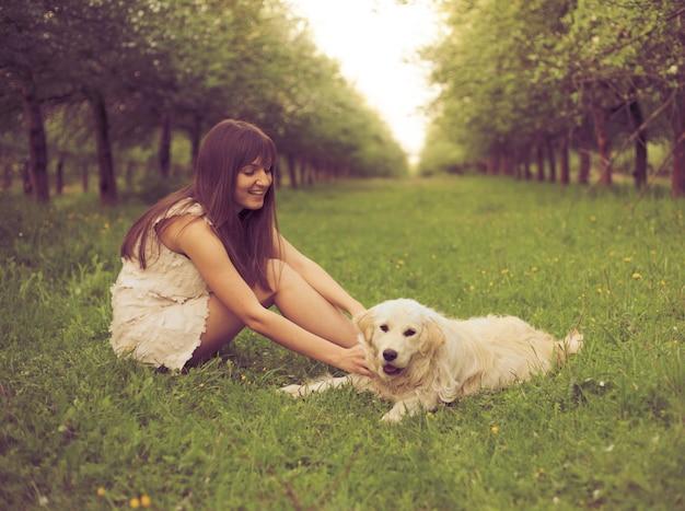 La ragazza gioca con il golden retriever nel parco