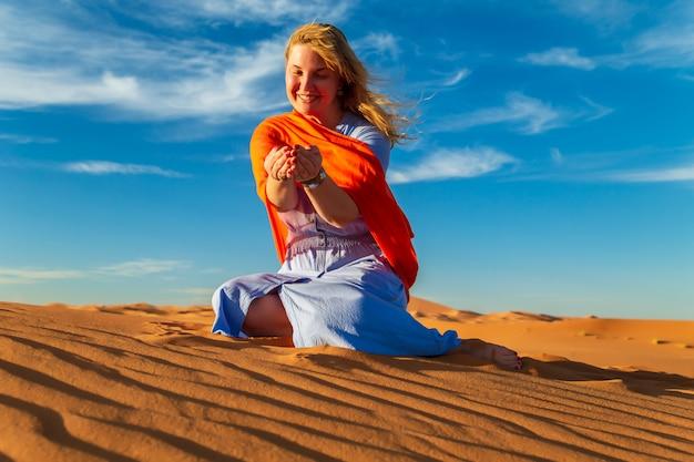 La ragazza gioca con la sabbia nel deserto del sahara. erg chebbi, merzouga, marocco.