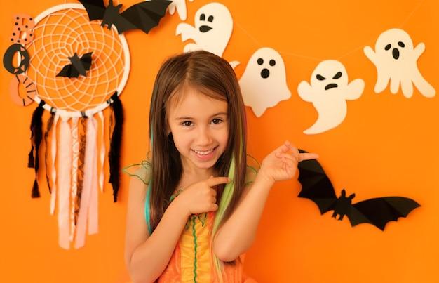 Ragazza che indica con le dita da parte allo spazio della copia su uno sfondo con decorazioni di halloween