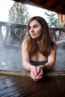 Ragazza in piscina con acqua calda in terrazza, trattamenti spa per il corpo. relax all'aria aperta, benessere. cottage con vasca idromassaggio. jacuzzi all'aperto. jacuzzi con una ragazza. bella figura di donna in costume da bagno
