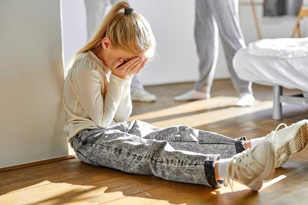 Ritratto di ragazza di bambino seduto da solo che soffre di crisi familiare, sostenendo dei genitori, concetto di conflitto familiare