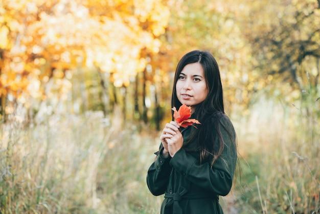Ritratto di ragazza con foglia rossa su sfondo giallo autunno bokeh.