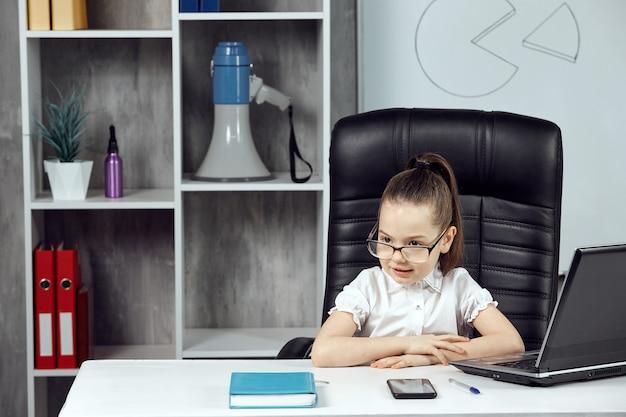 La ragazza ritrae il capo dell'agenzia a un tavolo bianco, in posa davanti alla telecamera