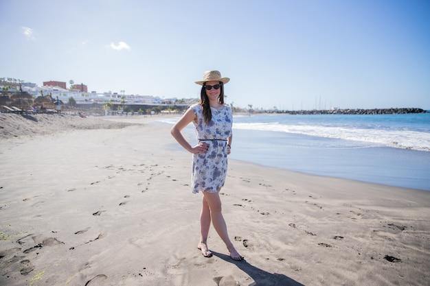Una ragazza posa in spiaggia indossando un cappello estivo e occhiali da sole, è su una bellissima spiaggia che sembra il paradiso.