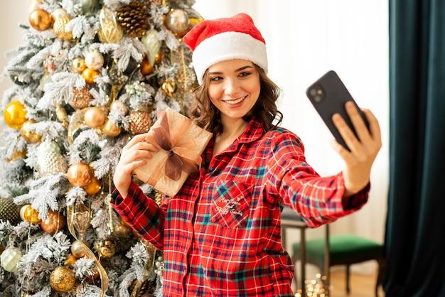 La ragazza posa e scatta un selfie vicino all'albero di natale. una donna si congratula per telefono con un parente online. ha in mano un regalo e sorride.